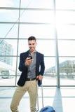 Homme de sourire se tenant dans la station avec le téléphone et la valise intelligents Image libre de droits