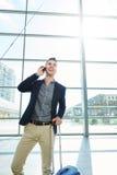 Homme de sourire se tenant dans la station avec le téléphone portable et la valise Photo stock