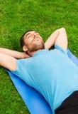 Homme de sourire se trouvant sur le tapis dehors Images libres de droits