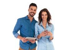 Homme de sourire stockant le service de mini-messages de comprimé et de femme au téléphone Images libres de droits