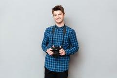 Homme de sourire tenant l'appareil-photo dans des mains photographie stock libre de droits
