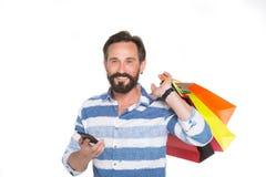 Homme de sourire tenant l'instrument moderne et mettre des achats sur l'épaule image stock