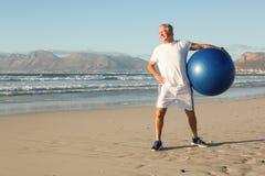 Homme de sourire tenant la boule d'exercice tout en se tenant à la plage Photographie stock
