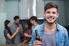 Homme de sourire tenant la bouteille à bière tandis qu'amis à l'arrière-plan Photographie stock libre de droits