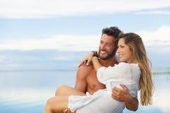 Homme de sourire tenant la femme dans des ses bras sous un ciel bleu sur le bord de la mer Images libres de droits