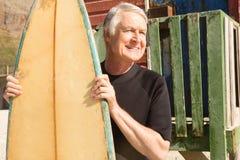 Homme de sourire tenant la planche de surf tout en se tenant contre la hutte de plage Image libre de droits