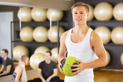 Homme de sourire tenant le medicine-ball tandis qu'amis se reposant dans le gymnase Image libre de droits