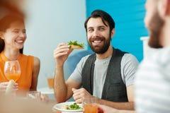 Homme de sourire tenant le pain tout en mangeant avec des amis Photos stock