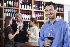 Homme de sourire tenant le verre à vin tandis qu'amis se tenant dans Backgrou Photographie stock libre de droits