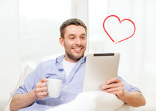 Homme de sourire travaillant avec le PC de comprimé à la maison Photos stock