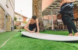 Homme de surfer avec le wetsuit cirant la planche de surf de femme Photo stock