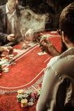 Homme de tabagisme jouant le tisonnier dans le casino Images libres de droits