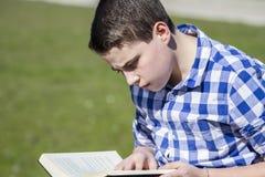 Homme de Teen.Young lisant un livre dans extérieur avec la pomme jaune. photos libres de droits