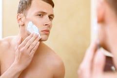 Homme de torse nu appliquant le moyen du rasage sur le visage Photographie stock