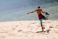Homme de touristes avec des appareils-photo jouant le football sur la plage Photos libres de droits