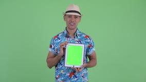 Homme de touristes ethnique multi heureux pensant tout en montrant le comprimé numérique banque de vidéos