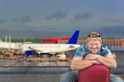 Homme de touristes s'asseyant avec la valise à l'aéroport Image stock