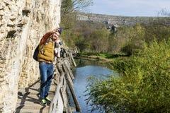 Homme de touristes se tenant sur un pont en bois avec son chien prenant des photos avec le téléphone Image libre de droits