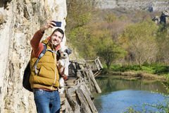 Homme de touristes se tenant sur un pont en bois avec son chien prenant des photos avec le téléphone Photographie stock