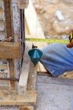 Homme de travail employant un plomb à plomb pour le contrôle Images stock
