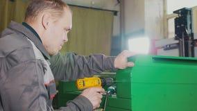 Homme de travailleur à l'aide d'un foret de main électrique - fabrication du trou dans la machine verte en métal image libre de droits