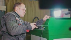Homme de travailleur à l'aide d'un foret de main électrique - fabrication du trou dans la machine verte en métal photo stock