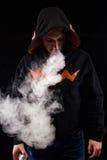Homme de Vaping dans le capot tenant un mod Un nuage de vapeur Image libre de droits