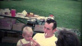 homme (de vintage de 8mm) tenant le bébé avec la cigarette dans la bouche banque de vidéos