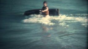 Homme (de vintage 8 superbe) essayant de monter l'échouer de scooter de mer banque de vidéos
