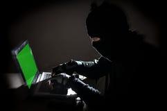 Homme de voleur entaillant l'ordinateur photographie stock libre de droits