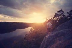 Homme de voyageur avec le sac à dos regardant le coucher du soleil près de la rivière Photo stock