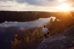 Homme de voyageur avec le sac à dos regardant le coucher du soleil près de la rivière Photographie stock