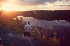 Homme de voyageur avec le sac à dos regardant le coucher du soleil près de la rivière dehors Images stock