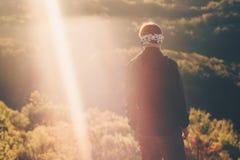 Homme de voyageur marchant aux montagnes de coucher du soleil images stock