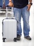 Homme de voyageur tirant la valise dans l'aéroport moderne Photographie stock