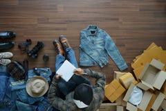 Homme de vue supérieure s'asseyant sur le plancher en bois et écrivant dans le carnet Images stock