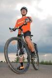 Homme de Yong avant de mettre en marche le vélo Photo stock