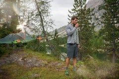 Homme debout buvant le camping accrochant proche de tente de boisson chaude au lac avec la lumière du soleil Groupe d'été de pers Photos libres de droits