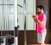 Homme debout de boucle de câble de biceps dans la machine de poulie photos libres de droits