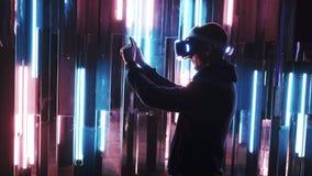 Homme debout essayant le casque de VR dans les lampes au néon banque de vidéos