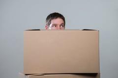 Homme derrière des carryboards sur le gris Image stock
