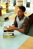 Homme derrière le compteur de bibliothèque Photographie stock