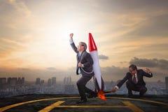 Homme des affaires deux jouant le jouet de fusée sur le haut toit de bâtiment avec s Photographie stock libre de droits