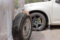 Homme des véhicules à moteur de mécanicien portant la roue de secours préparant le changement une roue de voiture Service des rép Photographie stock