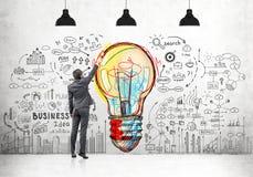 Homme dessinant des icônes d'ampoule et d'affaires Image libre de droits