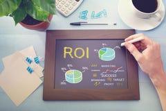 Homme dessinant le concept de ROI sur le tableau images stock