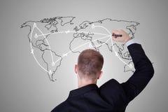 Homme dessinant une carte du monde Image stock