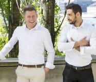 Homme deux bel dans des chemises blanches se tenant dehors Images stock