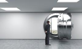 Homme devant le coffre-fort débloqué à la banque, dollars à l'intérieur Photo stock