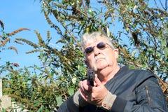 Homme dirigeant une arme à feu vers l'appareil-photo. Images stock